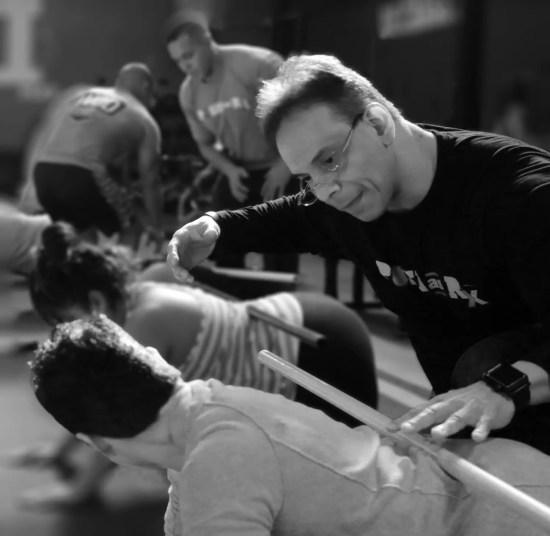 Image of Dr. Jimenez demonstrating rehabilitation exercises to patient.
