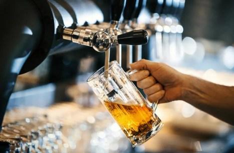 una pinta de cerveza que se vierte, lo que puede causar hinchazón
