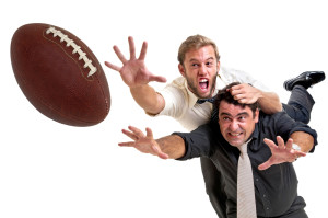 Businessmen playing rugby aka U.S. Football, isolated in white