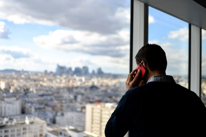 man in black top using red phone by glass wall