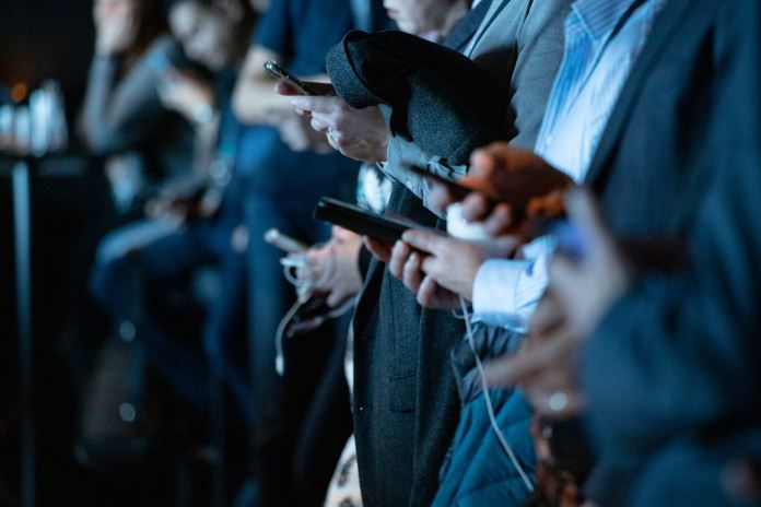 people using phone while standing
