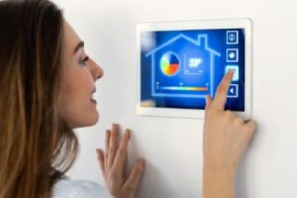 Young woman using the home automation system on digital tablet to check the security.