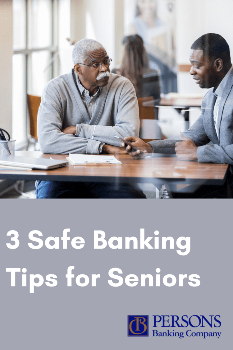 A senior citizen sits in a bank with a younger male employee who is helping him with safe banking.