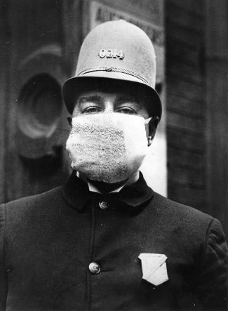 An American policeman wearing a 'Flu Mask' to protect himself from the outbreak of Spanish flu following World War I. (Photo by Topical Press Agency/Getty Images)