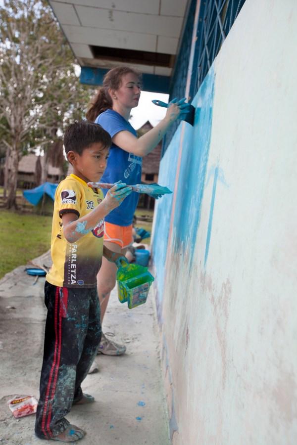 Volunteer tourists painting the school