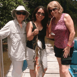 Three guests showing piranha catch for the day