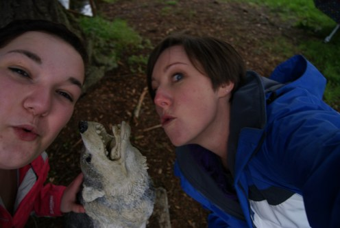 Mona and Kristine practice their howling with a wolf statue, which is much safer than a real wolf.