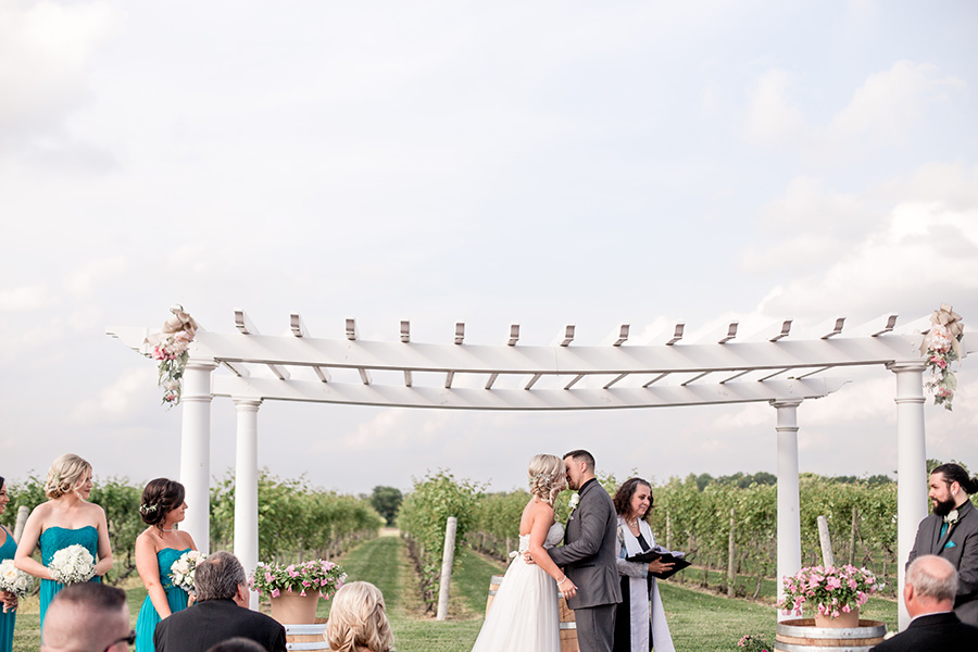 first kiss underneath pergola at tomasello winery