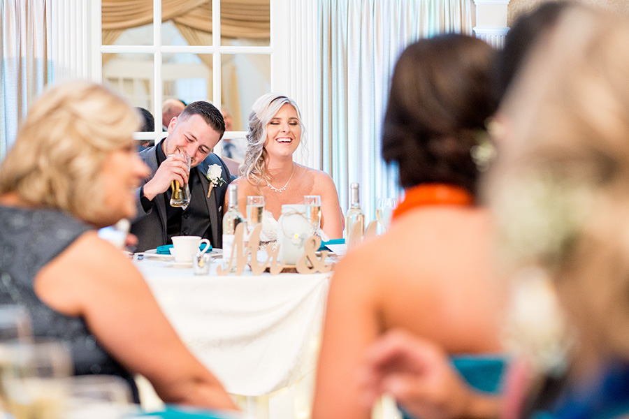 bride and groom laugh together at wedding reception