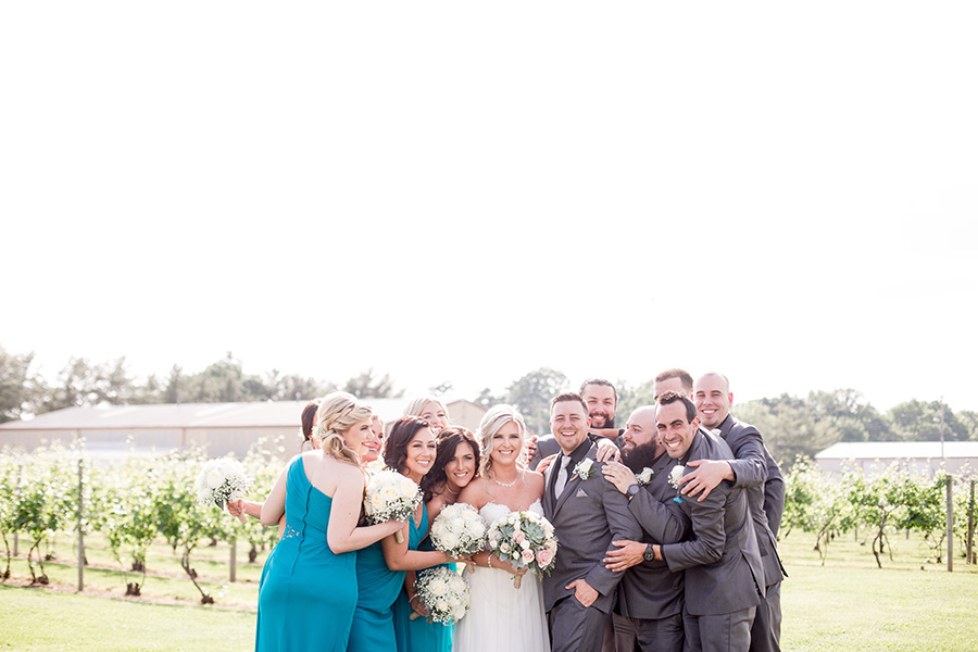 wedding portraits with the wedding party in the vineyards at tomasello winery