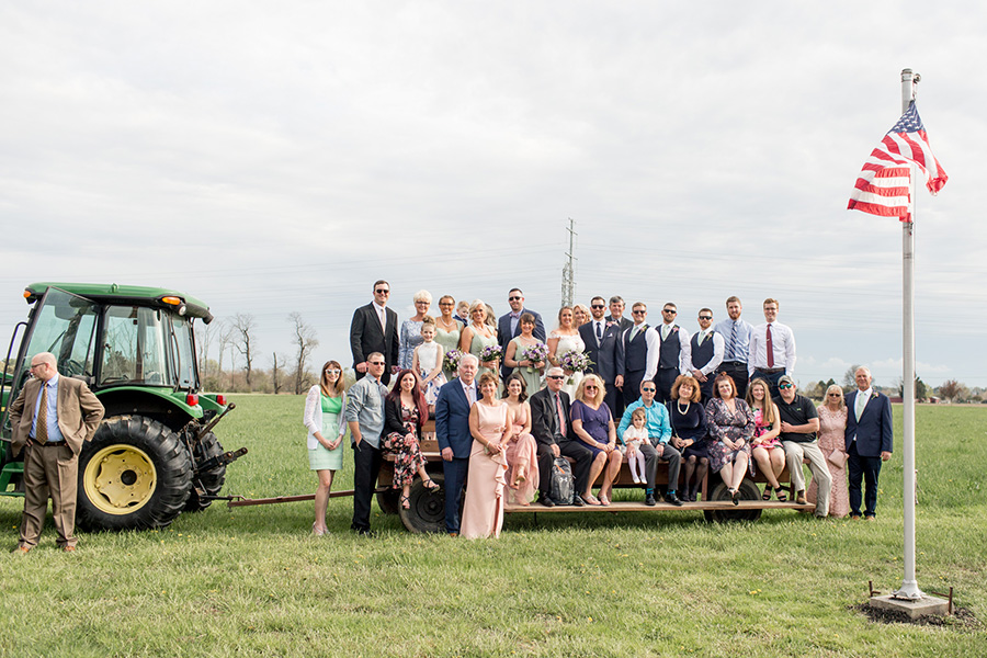 guests pose on tractor at rustic Warner Road Farm wedding