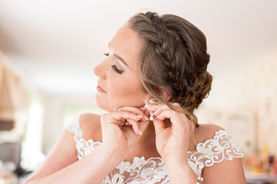 bride getting ready and putting on her jewelry