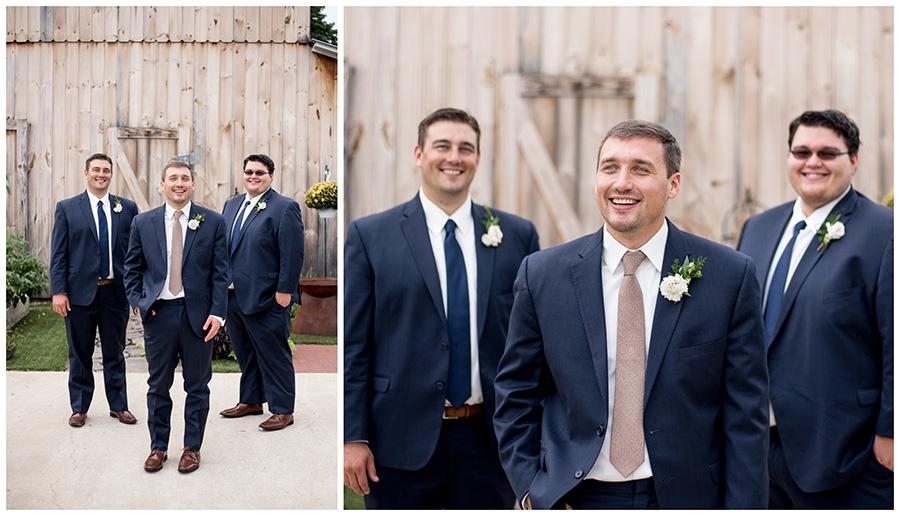 groomsmen pose with groom outside the barn
