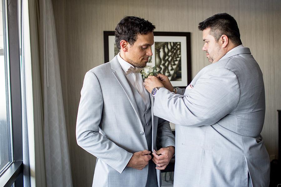 groom getting his flower pinned on