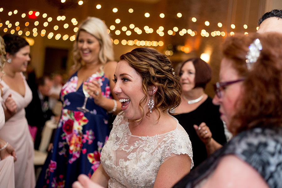 bride dances with her friends under the cafe lights at the reception