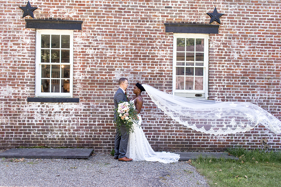 bride and groom near historic buildings at allaire