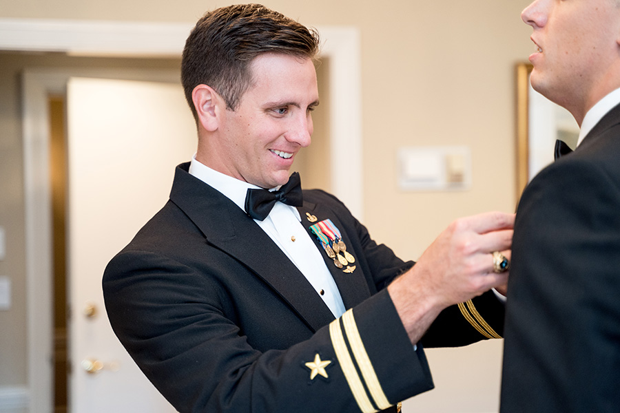groom straightening groomsman's tie