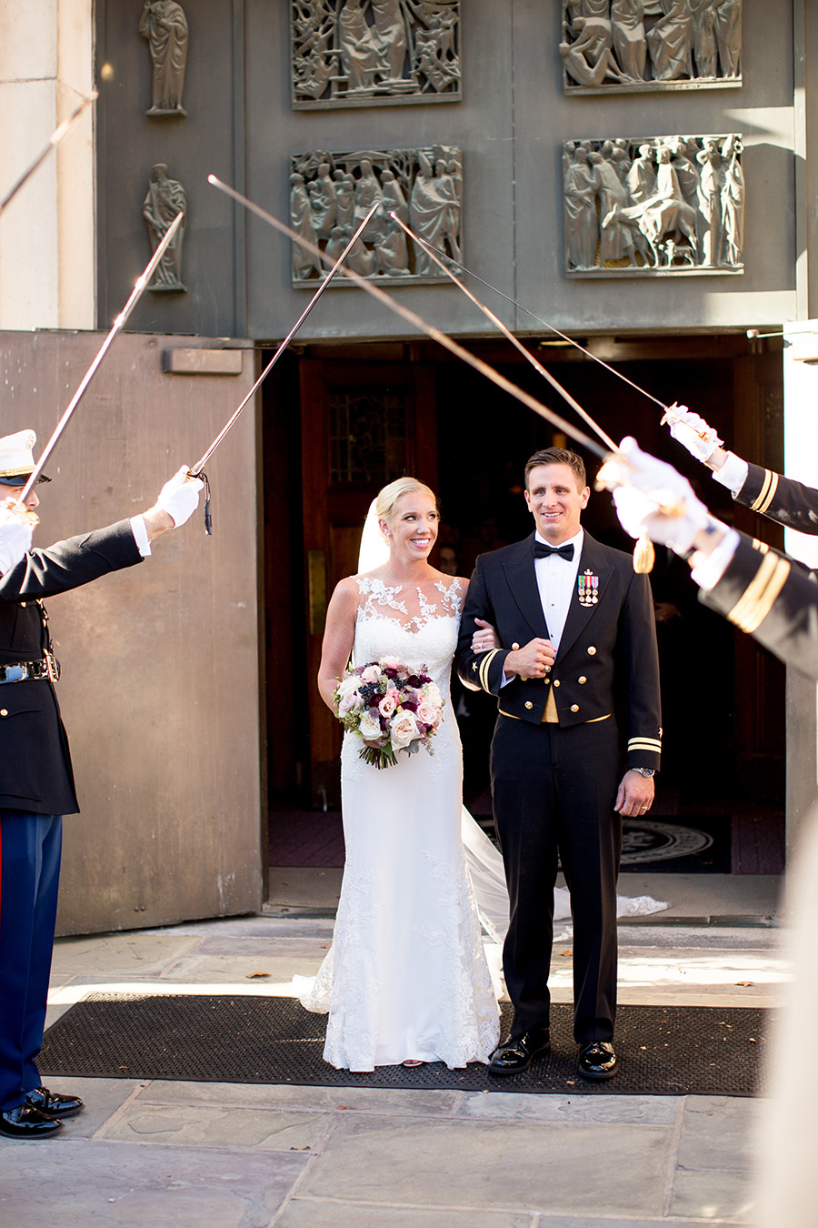 married couple stand before sword arch outside of church