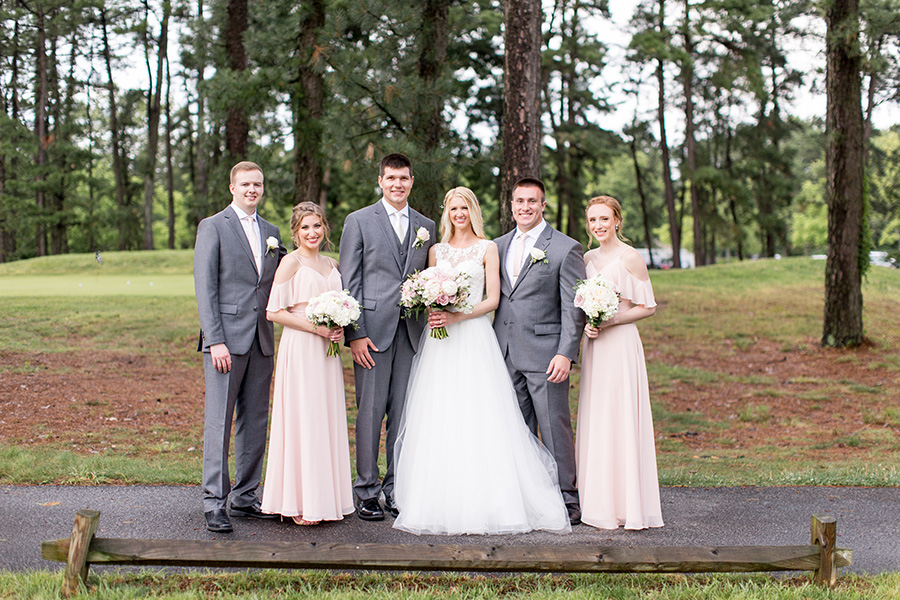wedding party standing near the pines on the golf course
