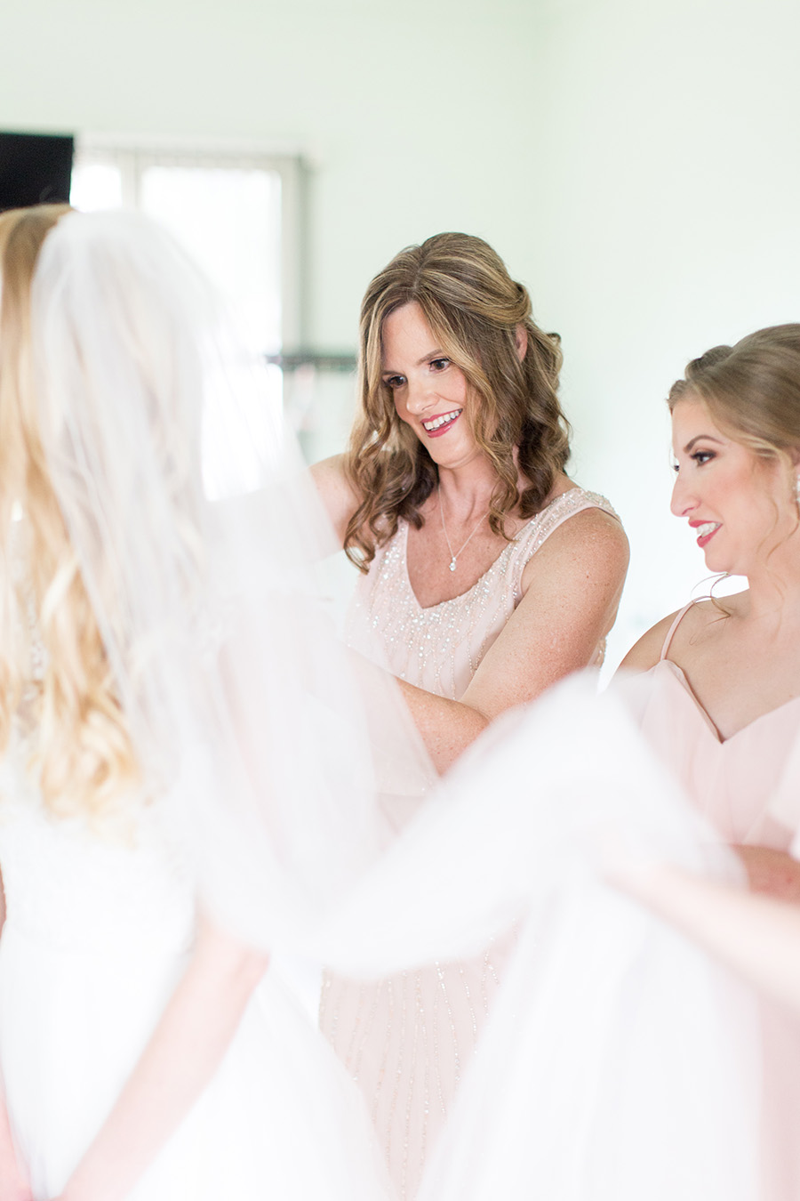 mother of bride helping bride with her dress