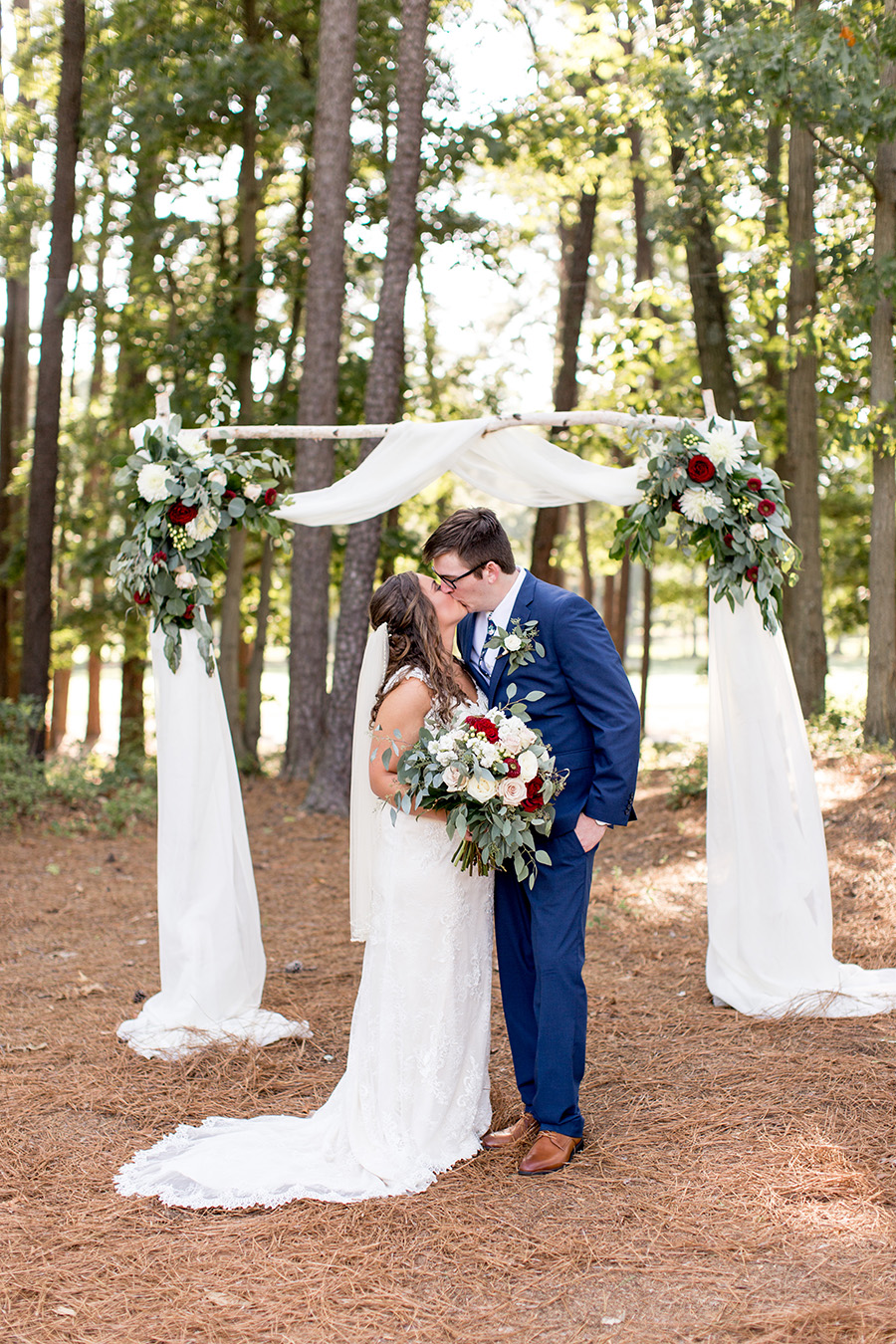 wedding couple kissing beneath their ceremony arch