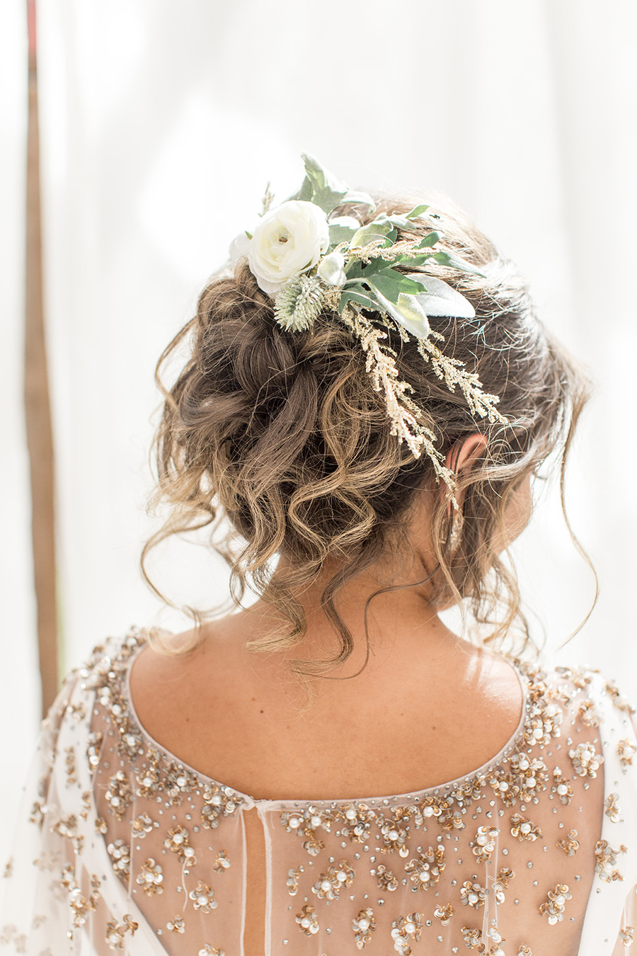 Messy wedding updo with floral hairpiece