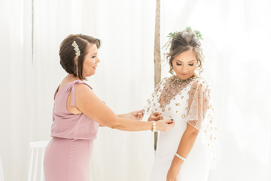 Mom helps bride into dress in the greenhouse at Bast Brothers