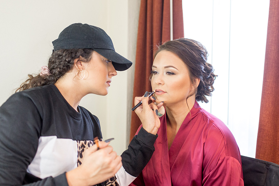 bride getting her makeup done in the hotel room