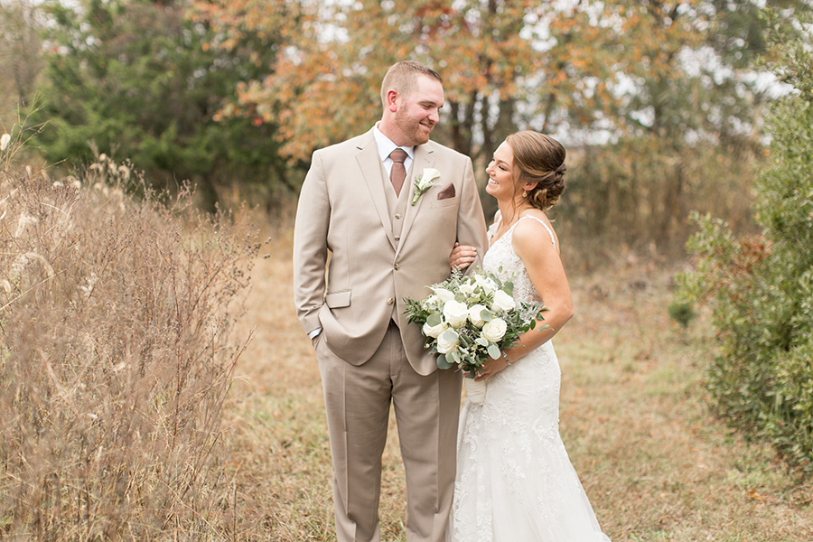Groom wearing light tan suit with orange tie with his bride
