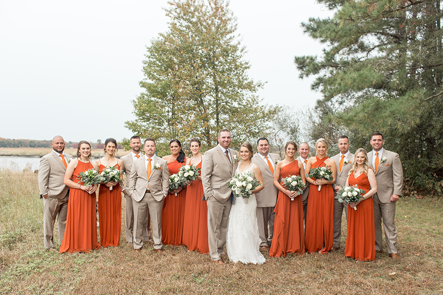 Wedding party in burnt orange dresses and tan suits at Eagle Manor