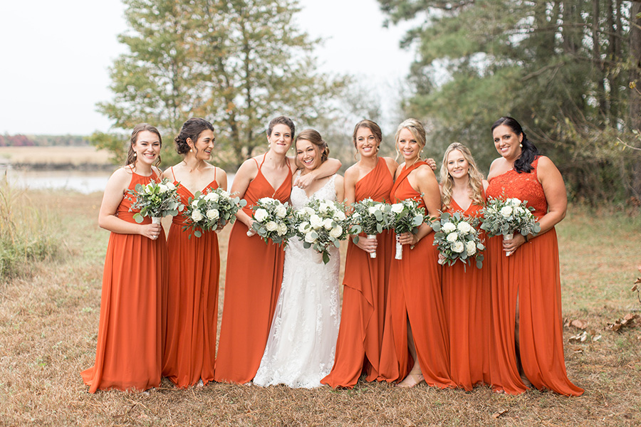 Bridesmaids in burnt orange floor-length dresses with white bouquets