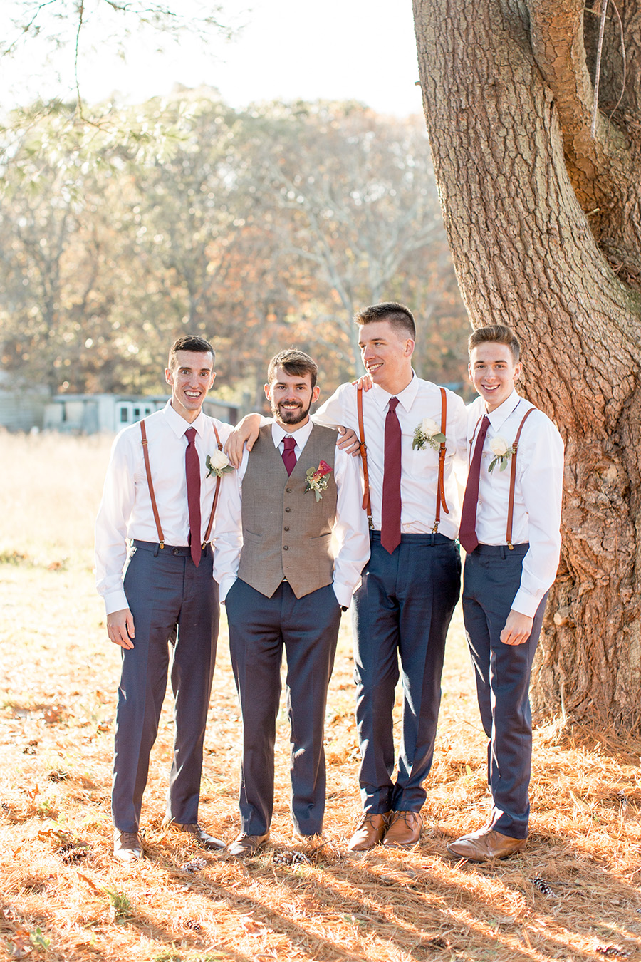 groom with his groomsmen in suspenders and navy pants