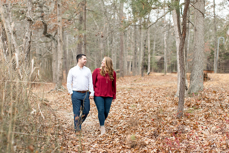 engaged couple walking in the woods at parvin state park