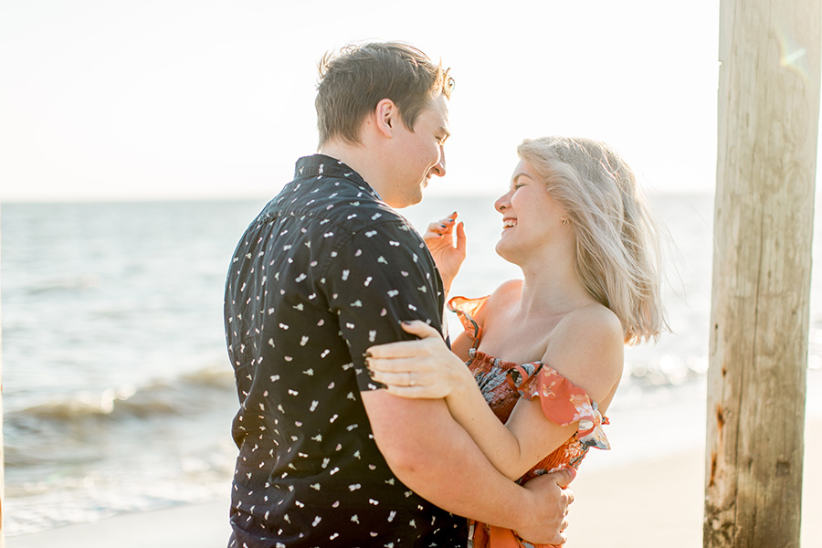engaged couple laughing together on the beach