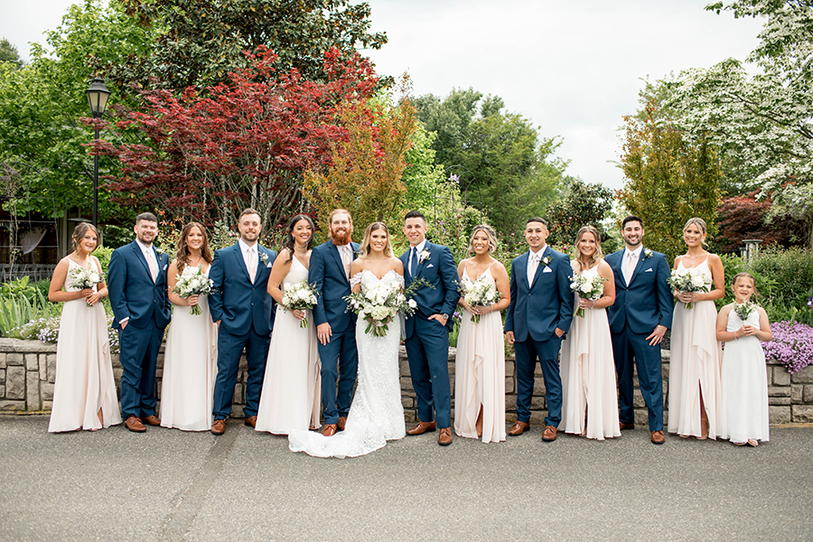the bridal party color palette was navy blue and blush with the bridesmaids carrying cream and white bouquets