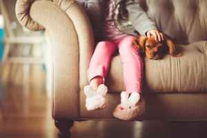 Little girl and dog laying on couch