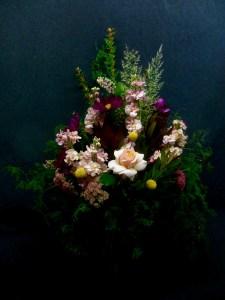 picture of arrangement with Cosmos, Stock, Sedum, Craspedia, lush greens framing one beautiful soft pink Rose.