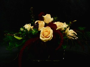 picture of wide oval vase filled with Amaranth, Roses and a variety of greens.