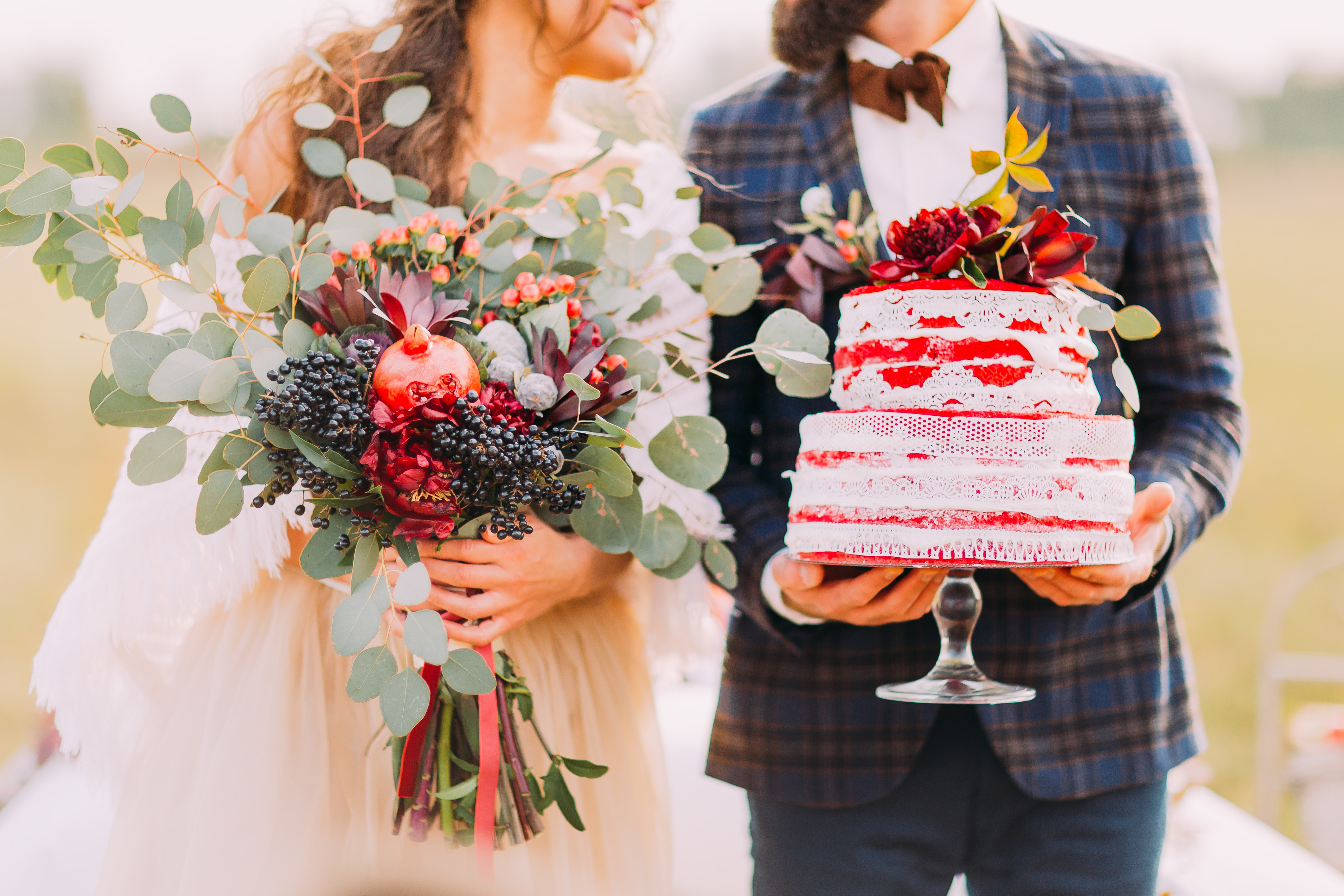 Wedding couple carrying rustic bouquet with berries and foliage and red tiers wedding cake adorned with flowers