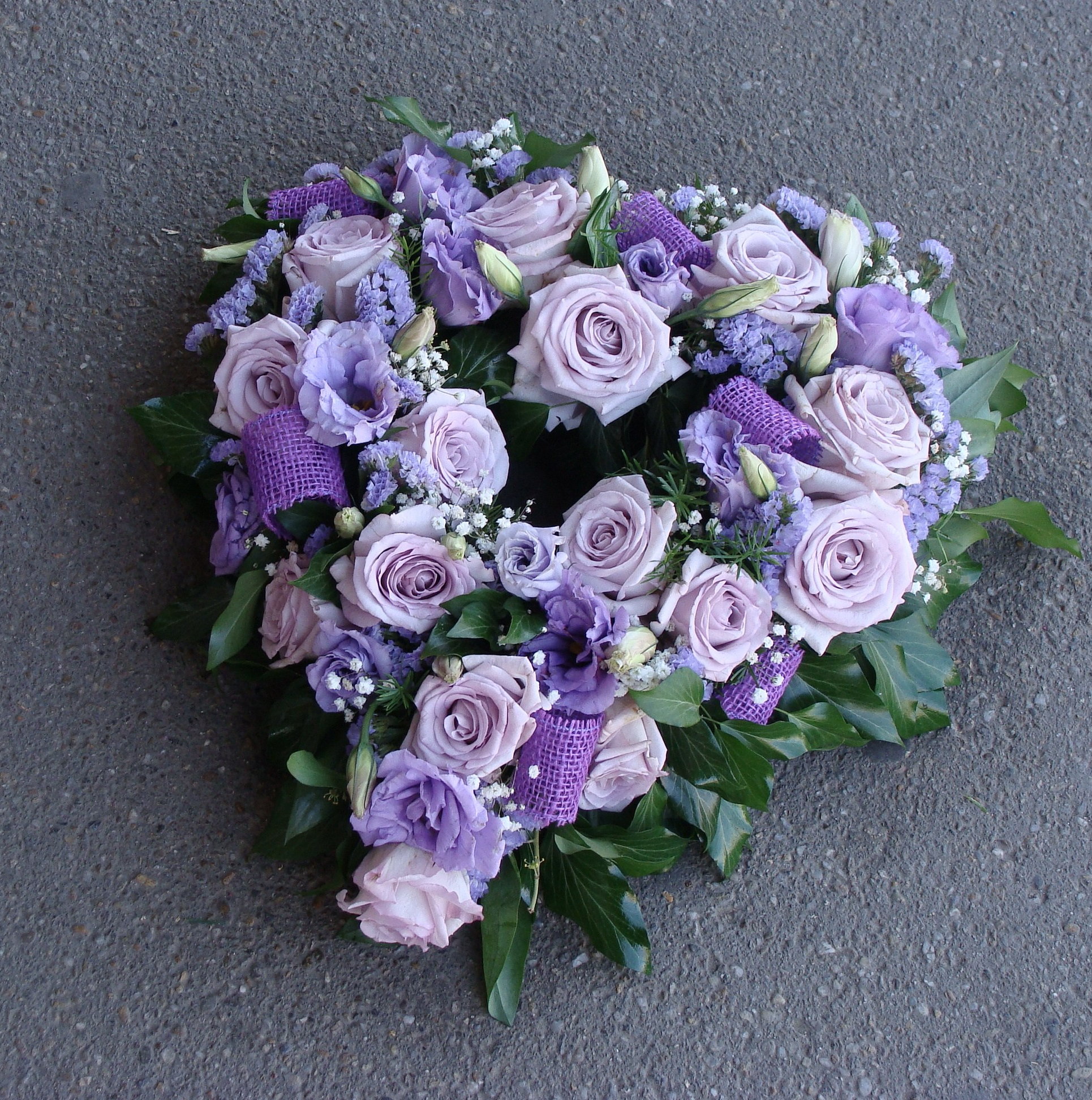 funeral wreath of lilac roses and purple ribbon