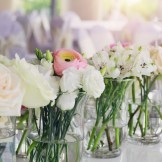 Wedding flower arrangement in matching glass vases with pink ranunculus and white roses