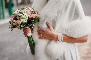 beige wedding bouquet at bride's hands in coat