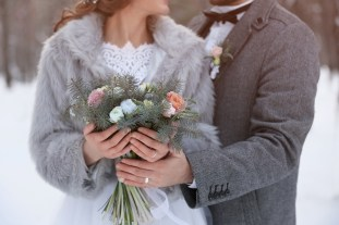 Happy wedding couple with bouquet outdoors on winter day, closeup