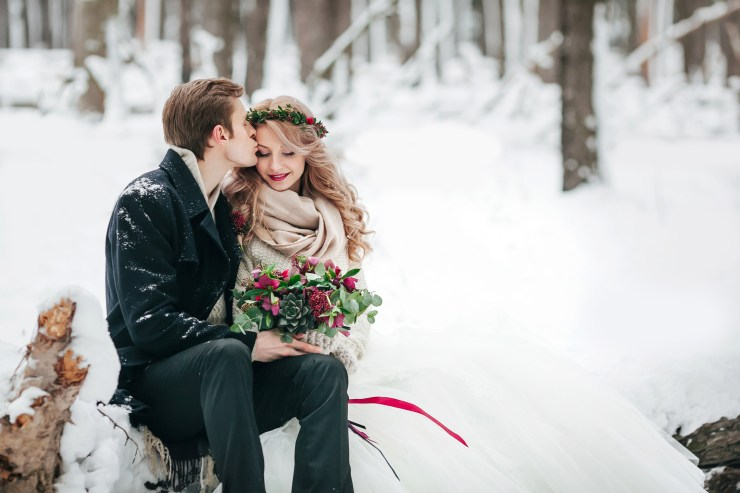 Groom is kissing his bride on the temple on background of the snowy forest. Winter wedding. Artwork