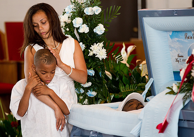 Interview with Andrew Nelles, Former Chicago Sun Times Photographer Erin Wells holds onto her son Robert D. Douglas Jr. 10 next to his fathers body during the funeral for Robert Douglas at Shiloh Missionary Baptist Church of Chicago in Chicago Ill. on Friday Jul
