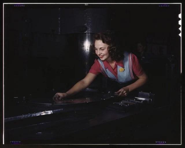 A woman preparing metal parts to go through a multi-ton hydropess. North American Aviation, Inc. 1942.
