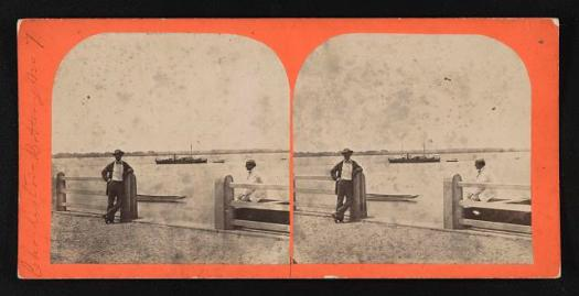 Photograph shows a view of Charleston harbor from the battery with a ship at anchor in the distance. One man leans against the fence post while another is seated on a bench.