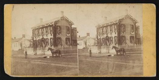 Photograph shows a street view Abraham Lincoln's home in Springfield, Illinois draped in mourning on the day of his funeral. A horse stands near a wooden plank from the street to the sidewalk.