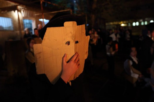 Orthodox boy watching the Lag B'Omer bonfire and using cardboard to protect himself from the heat of the fire.