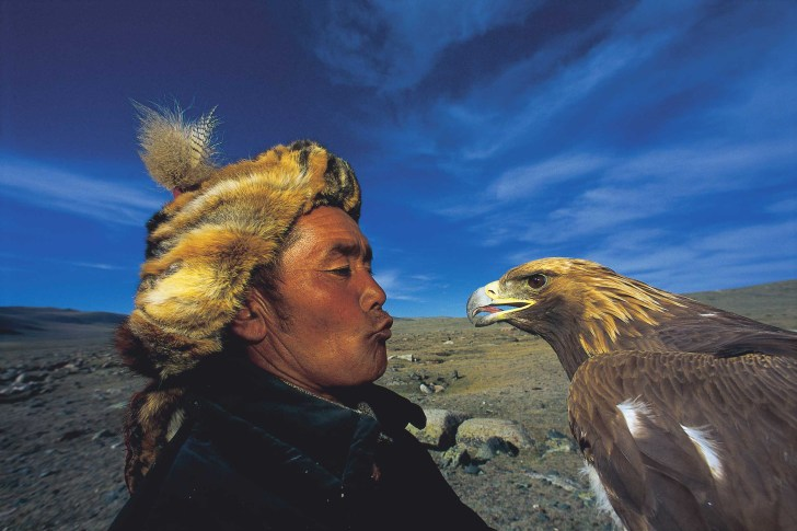 A Kazakh stands face to face with his golden eagle. Photograph by conservation photographer and cultural photographer Pete Oxford.